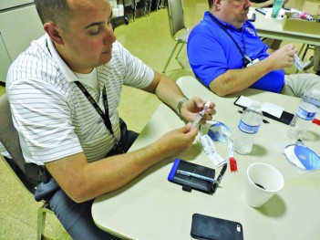 Times West Virginian photo by Richard Babich RESA 7 Public Service instructor Patrick Sanjulian assembles a Naloxone intranasal injector.