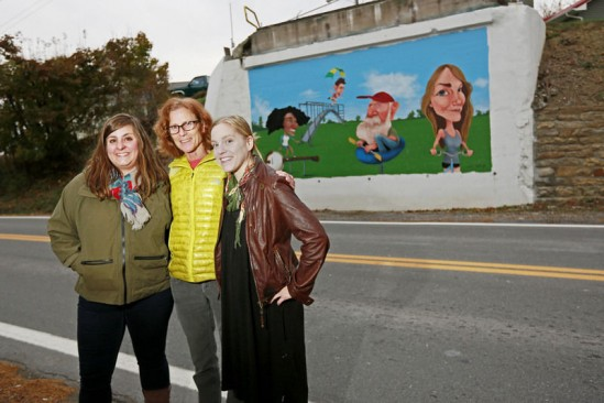 Register-Herald photo by Chris Jackson Rebecca Smith, from left, and Maura Kistler, both board members of the Fayetteville Arts Coalition, and Amanda Jane Miller, a local artist, stand in front of the second of two murals painted by muralist Jeff Pierson, a Charleston-based artist, at the location of the former Second Street Bridge in Fayetteville on Monday. Miller helped to render and fill in a lot of the mural, which the arts coalition helped implement.