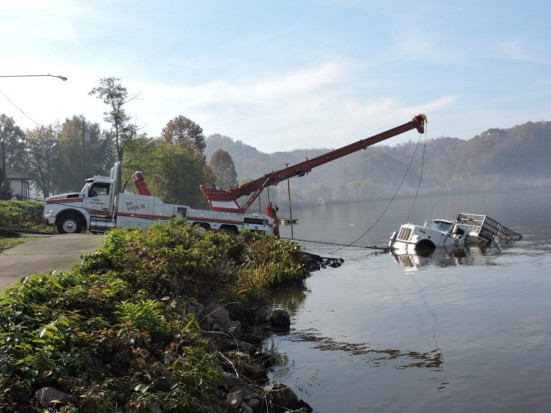 Intelligencer/Wheeling News-Register photo by Alan Olson Middle Creek Towing hauls a submerged water truck out of the Ohio River in Moundsville Wednesday morning.